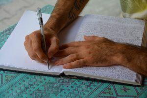 hands writing in a white paged notebook